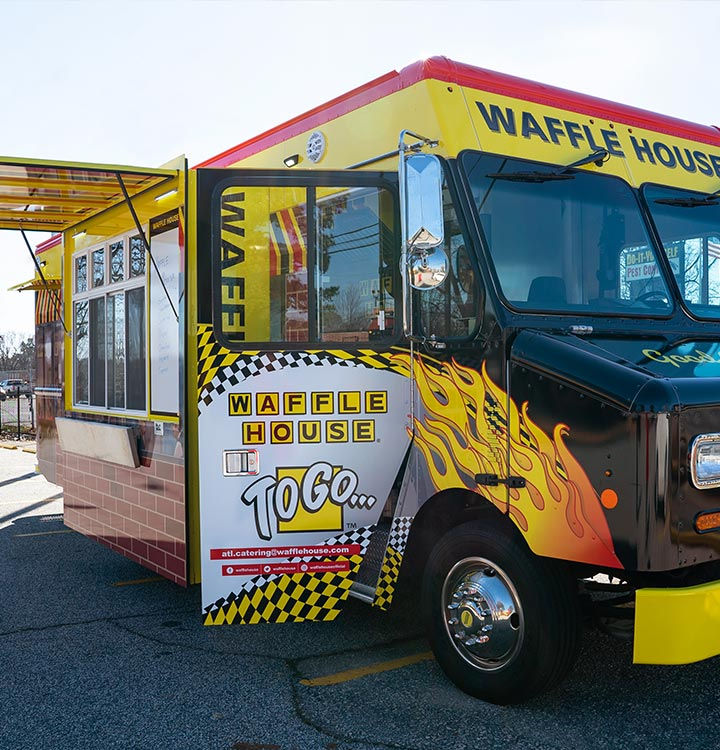 Young couple posing for wedding photos in front of Waffle House food truck