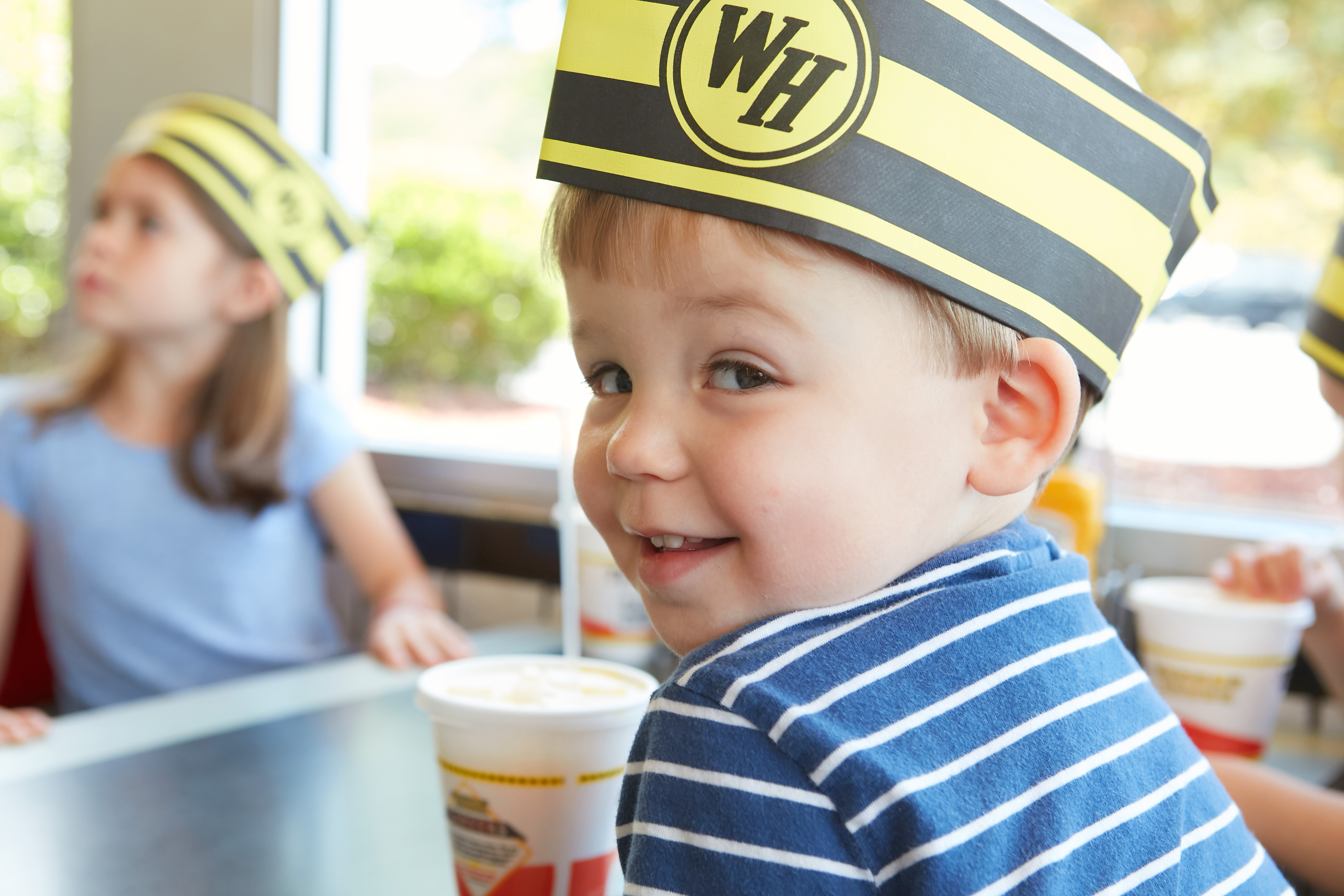 Small child wearing a waffle house hat
