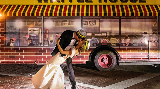 Groom kissing bride in front of Waffle House food truck